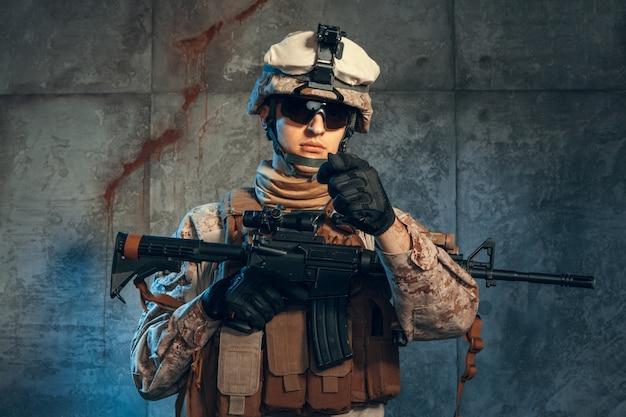 Forces spéciales soldat américain ou entrepreneur militaire privé tenant un fusil. image sur un fond sombre Photo Premium