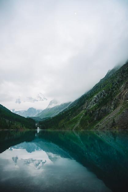 Forêt fantomatique près du lac de montagne tôt le matin. ruisseau de montagne du glacier se jette dans le lac. ondulation sur la surface de l'eau lisse. nuages bas. paysage de bois brumeux atmosphérique sombre. atmosphère tranquille. Photo Premium