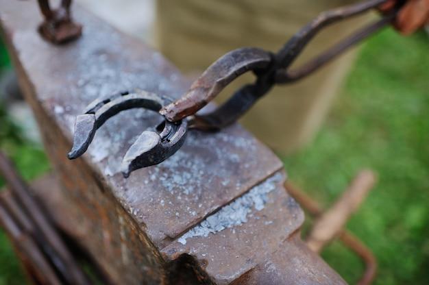 Le forgeron fait un fer à cheval sur l'enclume Photo Premium