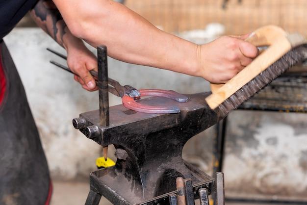Forgeron travaillant sur l'enclume, faisant un fer à cheval. Photo Premium