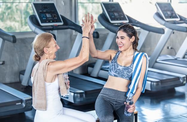 Formateur avec femme senior donnant highfive dans une salle de fitness. concept de mode de vie sain âgé Photo Premium