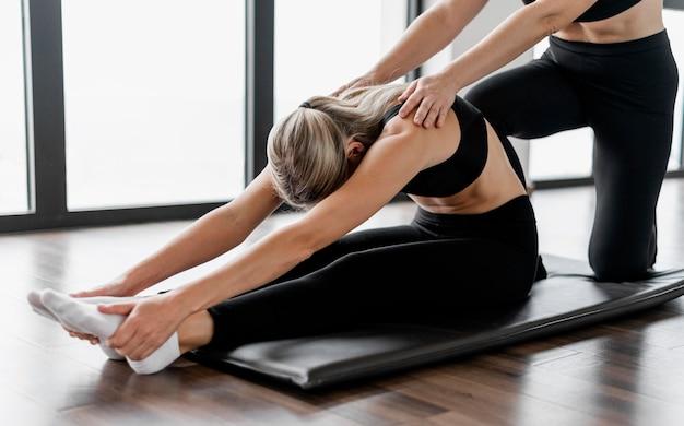 Formateur De Programme D'entraînement Et Client Assis Sur Un Tapis De Yoga Photo Premium