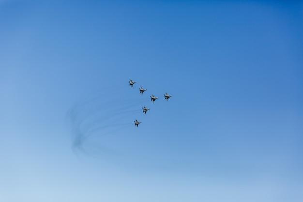 Une formation triangulaire d'un groupe de six avions de combat militaires russes volant haut dans le ciel bleu Photo Premium
