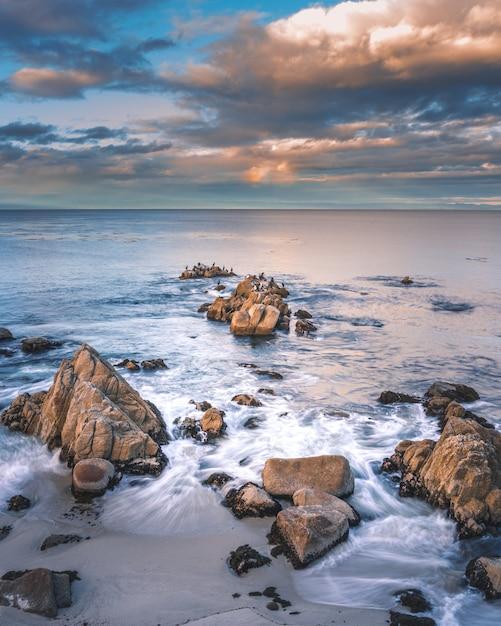 Formations Rocheuses Dans La Mer Sous Les Nuages Blancs Photo gratuit