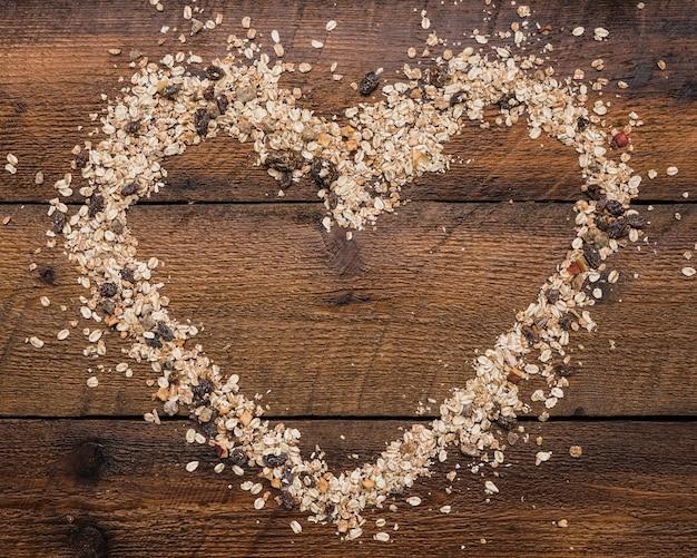 Forme de coeur fait avec de l'avoine et de la nourriture de noix sur la planche de bois Photo gratuit