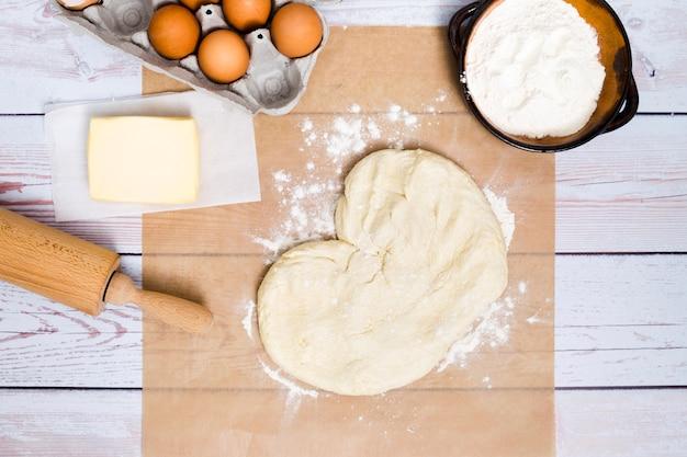 Forme de coeur faite de la pâte pétrie avec des ingrédients sur une planche en bois Photo gratuit