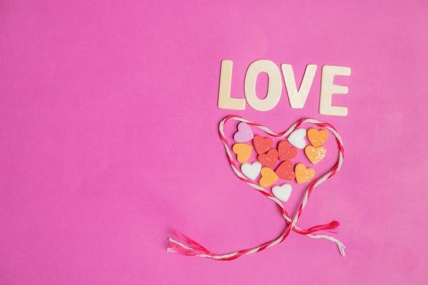 Forme de coeur, mot amour dans les coeurs rouges sur fond rose, icône de l'amour, saint valentin Photo Premium