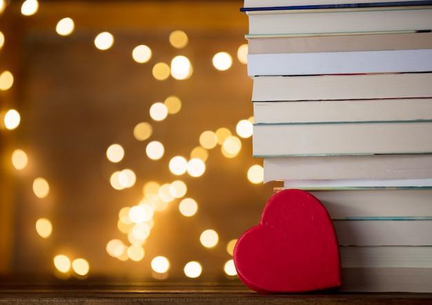 Forme de coeur près de la pile de livres et de guirlandes lumineuses Photo Premium