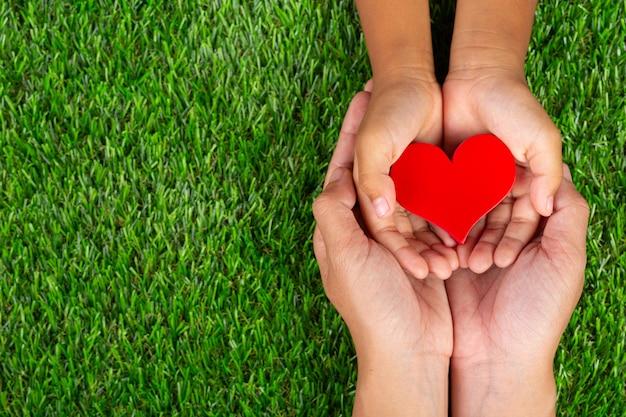 Forme De Coeur Rouge Dans Les Mains Des Membres De La Famille Tenant Photo gratuit