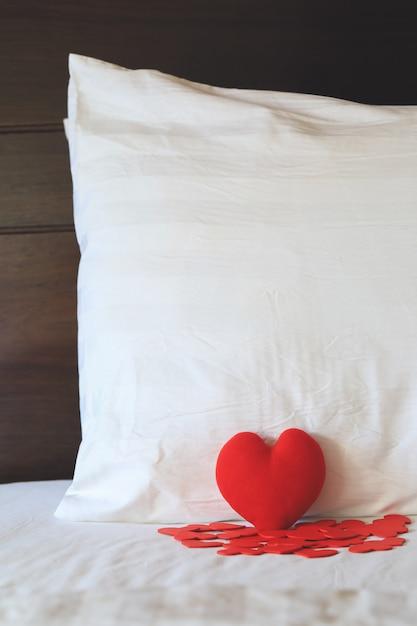 Forme de coeur rouge sur le lit et contre l'oreiller Photo Premium