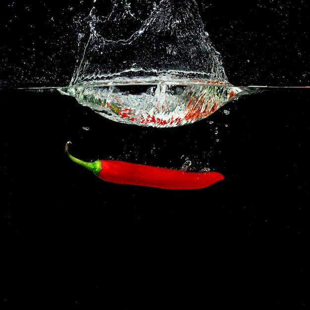 Forme d'éclaboussure de couronne d'eau par le piment rouge tombant dans l'eau Photo gratuit