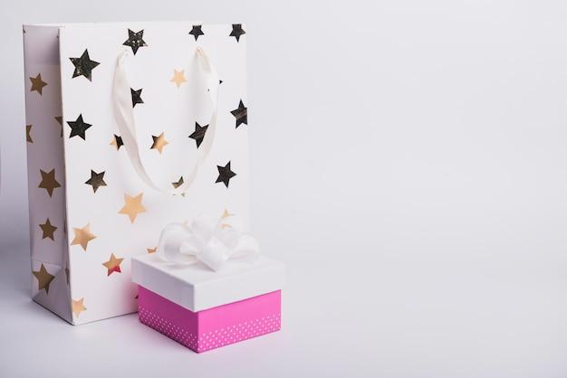 Forme d'étoile sur sac à provisions avec boîte-cadeau fermée isolé sur fond blanc Photo gratuit