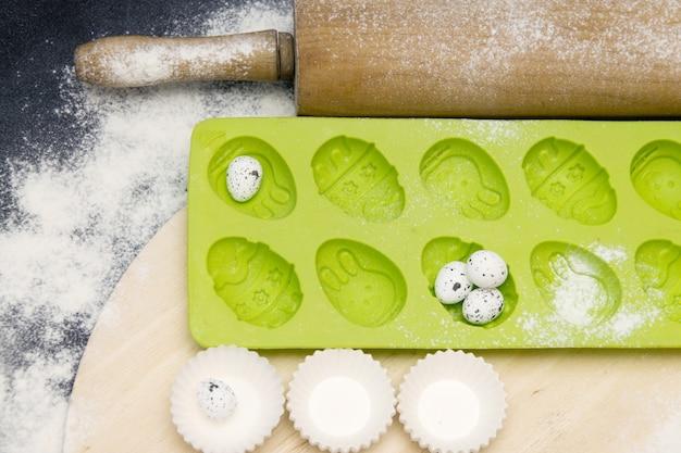 Forme verte en silicone pour la cuisson de petits gâteaux de pâques sur fond noir avec de la farine Photo Premium