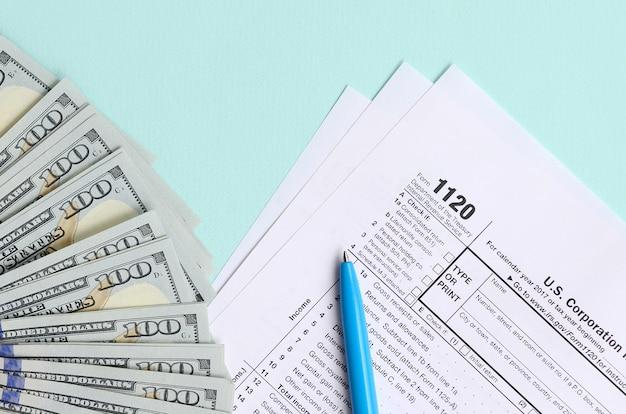 Formulaire 1120 d'impôt se trouve près de cent dollars et stylo bleu sur un bleu clair Photo Premium