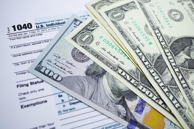 Formulaire de déclaration de revenus 1040 et billet en dollars: us individual income. Photo Premium