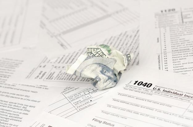 Formulaire de déclaration de revenus individuelle et billet de cent dollars froissé Photo Premium
