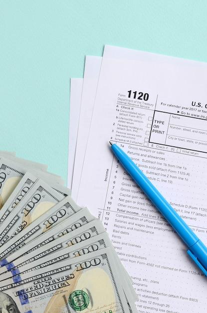 Formulaire d'impôt se trouve près de cent dollars et stylo bleu sur Photo Premium