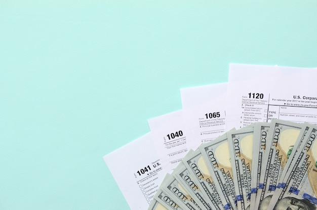 Les formulaires fiscaux se trouvent près de cent dollars et d'un stylo bleu sur un fond bleu clair. déclaration d'impôt sur le revenu Photo Premium