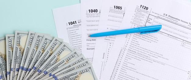 Formulaires d'impôt se trouve près de cent dollars et stylo bleu Photo Premium