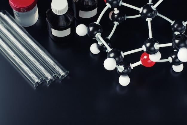 Formule moléculaire et équipement de laboratoire sur un fond sombre. science concept de chimie organique Photo Premium