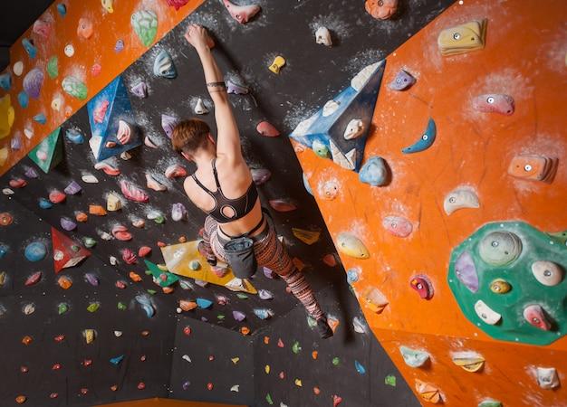 Forte grimpeuse femelle sur un mur d'escalade de rocher intérieur atteint le sommet Photo Premium