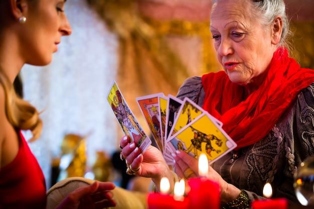Fortuneteller établissant des cartes de tarot avec le client Photo Premium