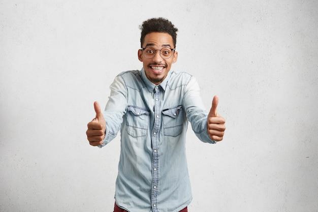 Fou De Joie, Jeune Homme Aux Cheveux Hirsutes, Moustache, Lève Les Pouces, Montre Le Signe Ok, étant Délicieux Avec Les Résultats Des Examens D'entrée, Photo gratuit