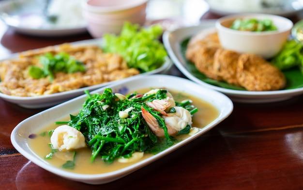 Fougère légume avec crevettes dans un plat blanc sur une table en bois Photo Premium