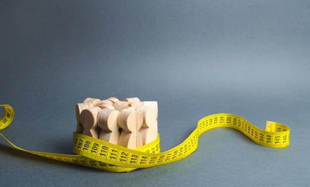 Une foule de personnages en bois saisis par un ruban à mesurer. Photo Premium