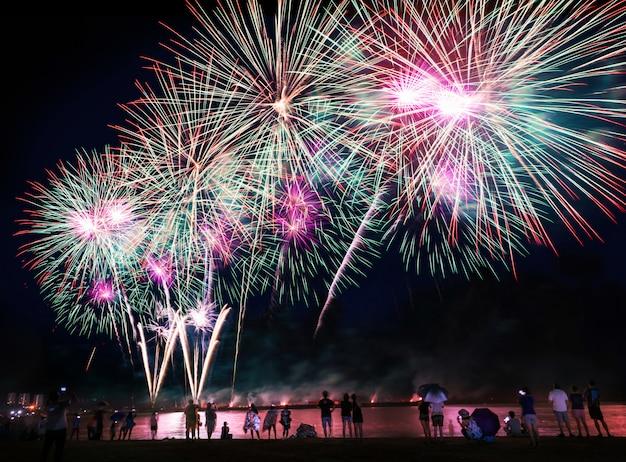 Foule regardant des feux d'artifice sur la plage Photo Premium