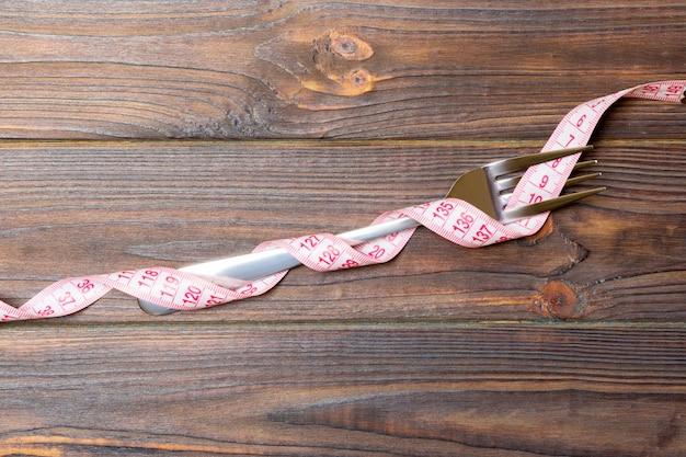 La fourche est enveloppée dans du ruban à mesurer sur du bois Photo Premium