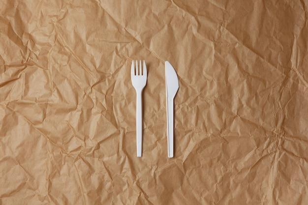 Fourchette Blanche Recyclable Réutilisable, Couteau à Base D'amidon De Maïs Ou D'avoine Sur Papier Kraft Froissé Brun, Espace Copie Photo Premium