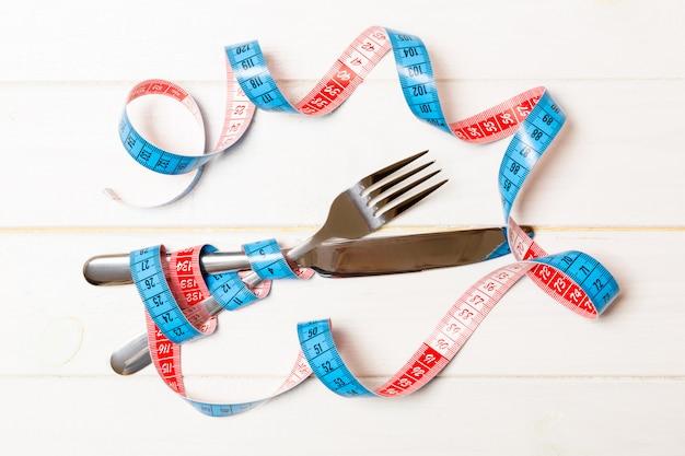 Fourchette et couteau croisés sont enveloppés dans du ruban à mesurer sur un fond en bois. Photo Premium