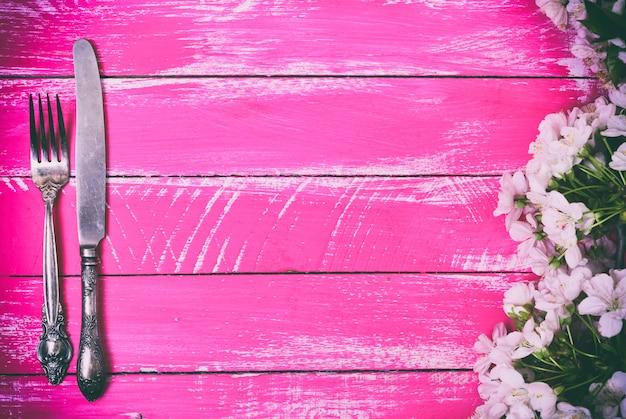 Fourchette et couteau en fer sur un fond en bois rose Photo Premium