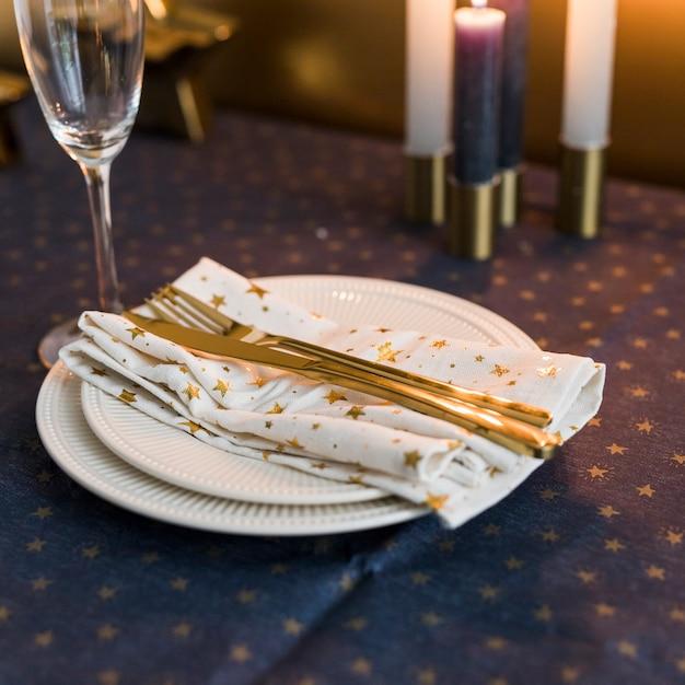 Fourchette et couteau en or sur plaque blanche Photo gratuit