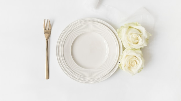 Fourchette; plaque de céramique; roses et ruban de satin sur fond blanc Photo gratuit