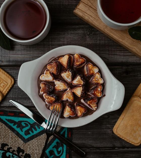 Fourchette prête à cueillir un biscuit en forme de cœur finement cuit dans un plat blanc Photo gratuit