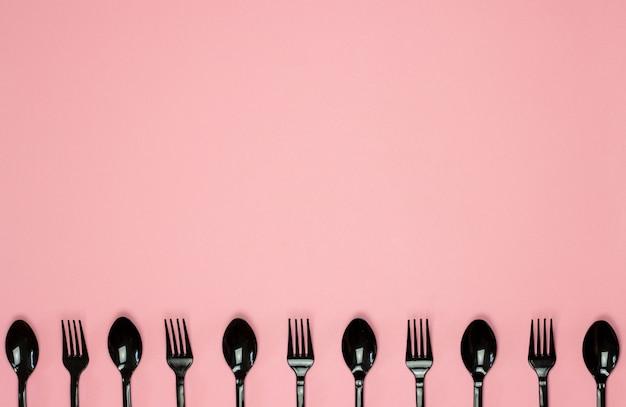 Fourchettes et cuillères sur fond rose. concept minimal. sans plastique. Photo Premium