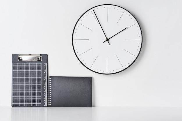 Fournitures de bureau, horloge collante et ronde sur blanc Photo Premium