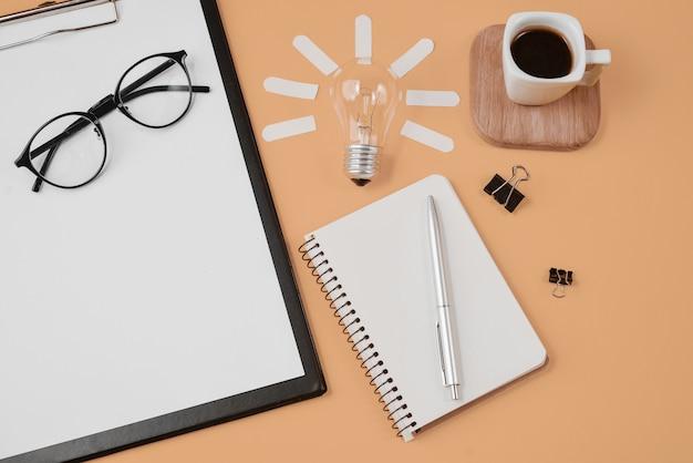 Fournitures de bureau de style bureau avec stylo, bloc-notes, lunettes, tasse à café et ampoule Photo Premium