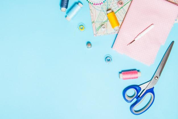 Fournitures de couture, patron et accessoires pour travaux d'aiguille sur fond bleu, coutures, broderies. espace pour le texte. lay plat, vue de dessus. Photo Premium