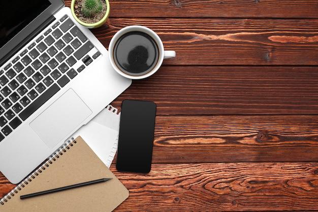 Fournitures et matériel de bureau sur une table en bois sombre Photo Premium