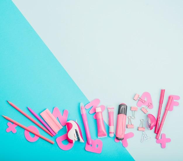 Fournitures scolaires et alphabets roses sur fond bicolore Photo gratuit