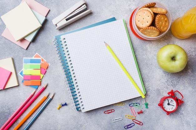 Fournitures scolaires et biscuits salés, jus d'orange et pomme fraîche Photo Premium