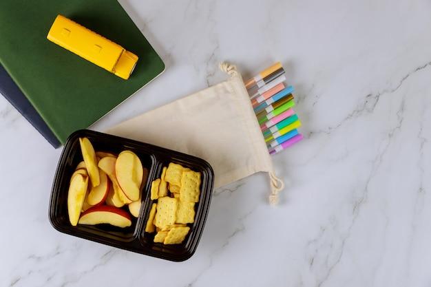 Fournitures Scolaires Et Boîte à Lunch Avec Pomme Tranchée Et Craquelins Photo Premium