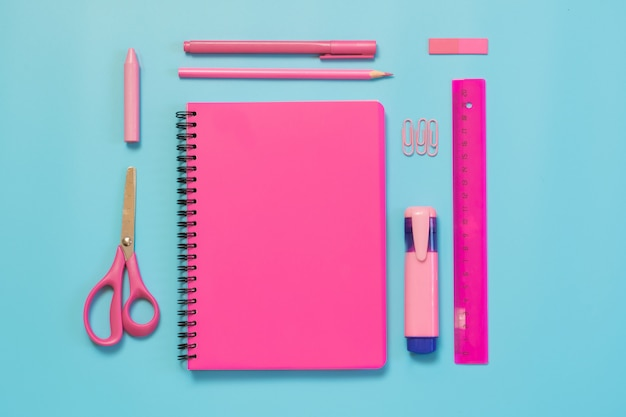 Fournitures scolaires, cahiers et stylos roses sur bleu vif. vue de dessus, plat poser. espace de copie. Photo Premium