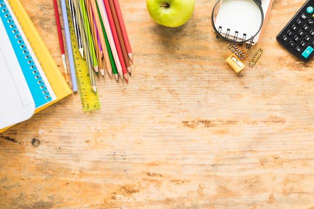 Fournitures scolaires colorées sur fond en bois Photo gratuit