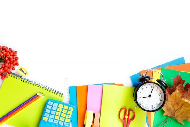 Fournitures scolaires colorées, livre et réveil sur blanc. Photo Premium