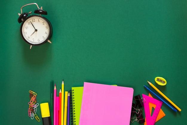 Fournitures scolaires colorées, livre et réveil sur le vert. Photo Premium