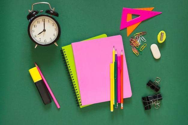 Fournitures scolaires colorées, livre rose et réveil sur vert. Photo Premium